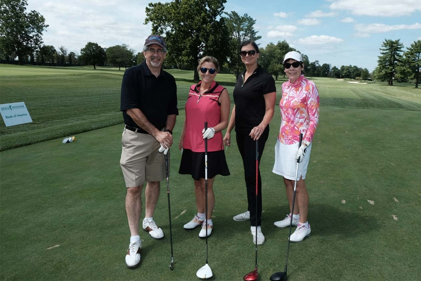 Foursome playing golf. Overlook Annual Golf Tournament Rescheduled